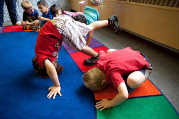 Children making floor shapes in classroom