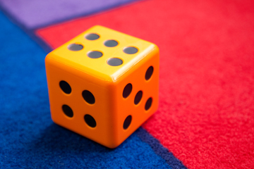 Picture of a colorful die on a colorful carpet