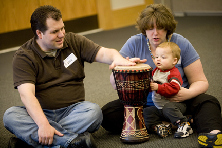 Parents with baby keep beat on drum