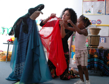 Katherine Lyons shows a child how to tell a story through props in a classroom