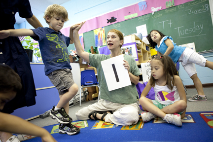 Laura Schandelmeier works with a little boy on dance concepts in classroom