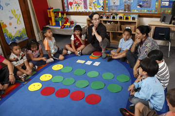 Rachel Knudson demonstrates graphing with vinyl spots in a classroom with children
