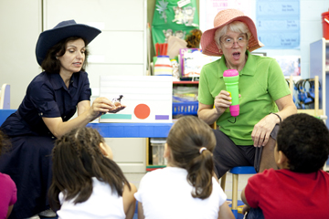 Sue Trainor sings with a teacher and children in a classroom