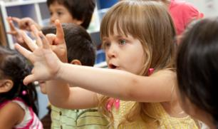 Children holding up fingers to count in a classroom