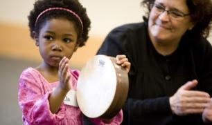 Child and caregiver keep beat on frame drum