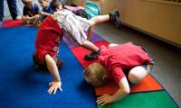 Children making floor shapes in classroom