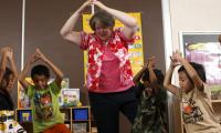 Teacher and children make body shapes in classroom