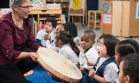 Teacher gives children turns beating a frame drum