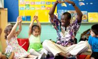 Kofi Dennis doing a warm-up in a classroom with children
