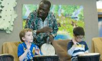 Kofi Dennis sings and drums with children in class