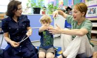 Laura Schandelmeier works on body shapes with a child and a teacher in a classroom