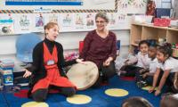 Laura Schandelmeier in a classroom with children and teacher