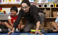 Rachel Knudson lays out vinyl spots in a classroom with children