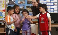 Rachel Knudson helps children count in a classroom