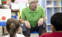 Stock photo of Sue Trainor in a classroom with two children