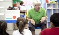 Sue Trainor in classroom with teacher and children